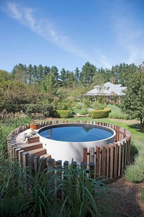 a round white pool with a staircase and a fence surrounding this pool to highlight it