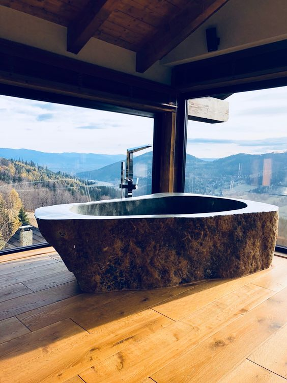 a rustic bathroom with a fantastic view, wooden floors and a dark stone bathtub carved of a single piece of stone