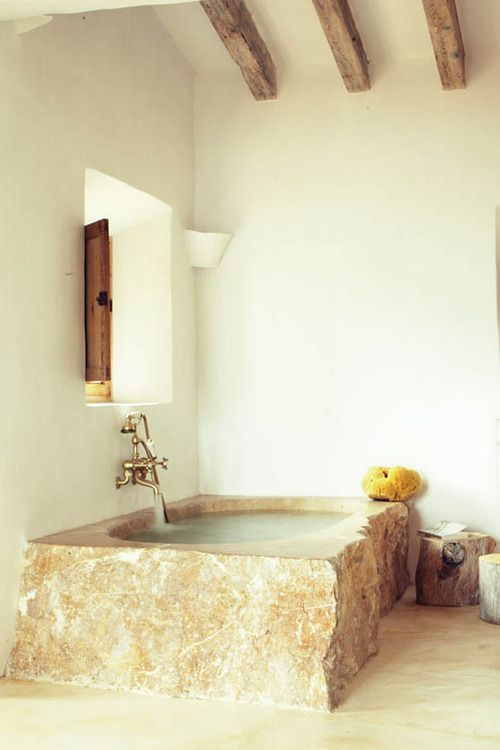 a rustic bathroom with white walls, wooden beams, a rough stone bathtub in a warm shade and tree stumps as side tables