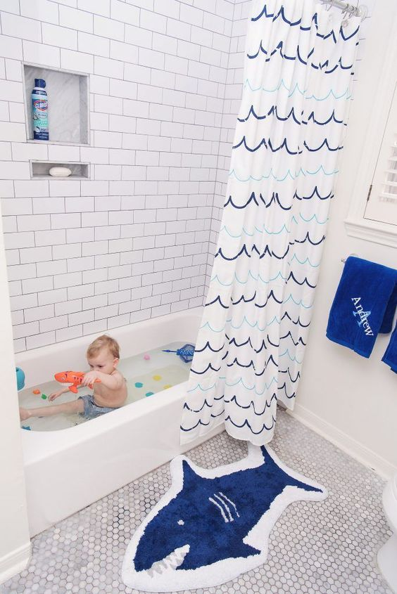 a sea-inspired kids' bathroom with a shark rug, a catchy wave curtain, blue towels for a chic and stylish look