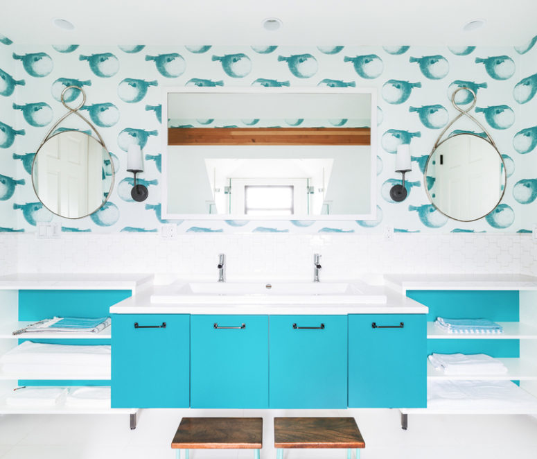 a sea-inspired kids' bathroom with funny fish wallpaper, a bright blue vanity and open shelving
