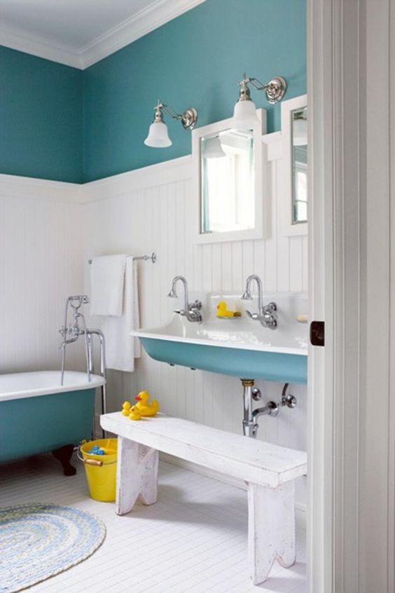 a serene kids' bathroom in blue, white and yellow, with color block walls and bright touches