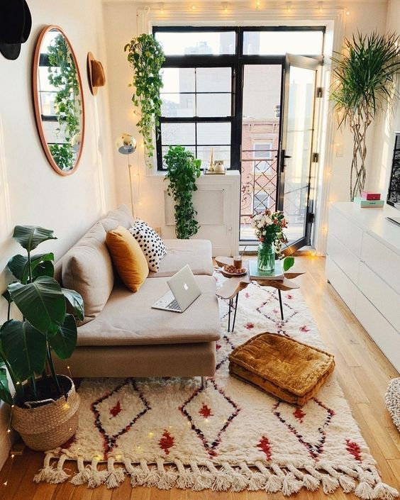 a small boho space with prints, rust touches, lots of potted greenery and string lights all over