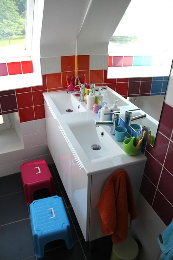 a small modern kids' bathroom with colorful tiles on the walls and bright stools plus bright accessories