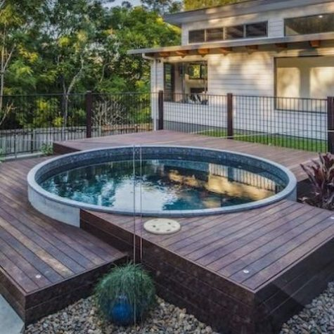 a small wooden deck with a round plunge pool that look very welcoming and stylish together