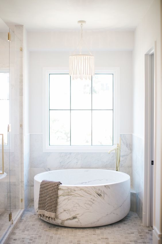a small yet refined neutral bathroom clad with marble tiles, with a marble half wall and a marble round bathtub