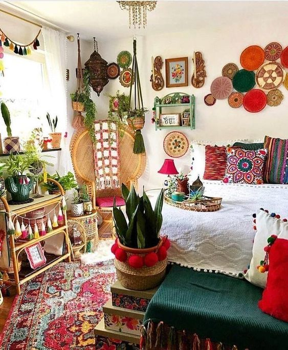 a super colorful boho bedroom with decorative plates, potted plants, colorful tassels and throws plus pompoms for decor