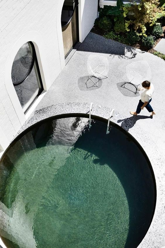 a super stylish minimalist backyard done with stone and concrete, with a round pool clad with stone