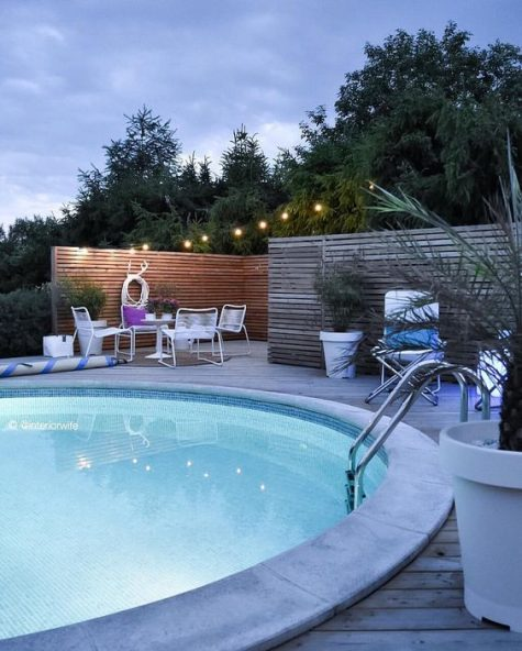a welcoming contemporary space with metal furniture and a large round pool with inner lights looks inviting
