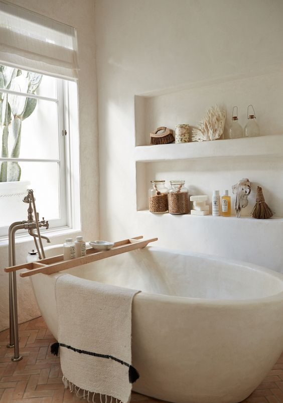 a white bathroom totally clad with plaster, with built-in shelves and with a white stone bathtub