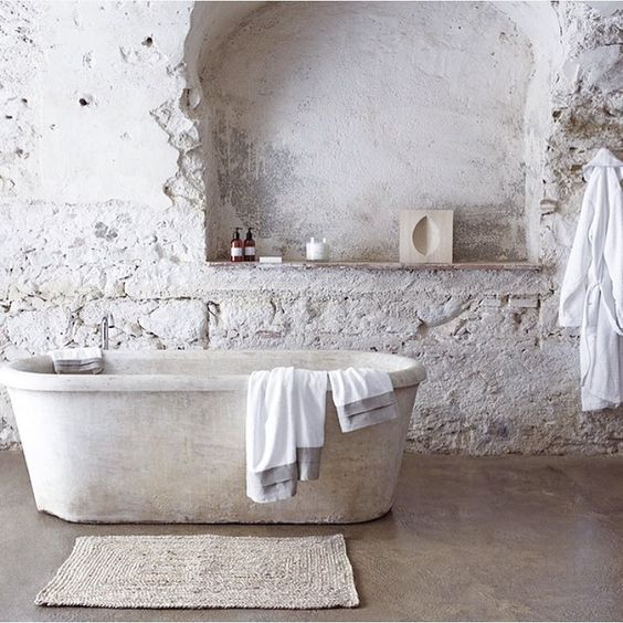 a white bathroom with rough stone tiles, a white stone bathtub and a jute rug is all-natural and relaxing