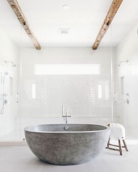 an all-white bathroom with a grey stone bathtub, wooden beams that make the space warmer and catchier