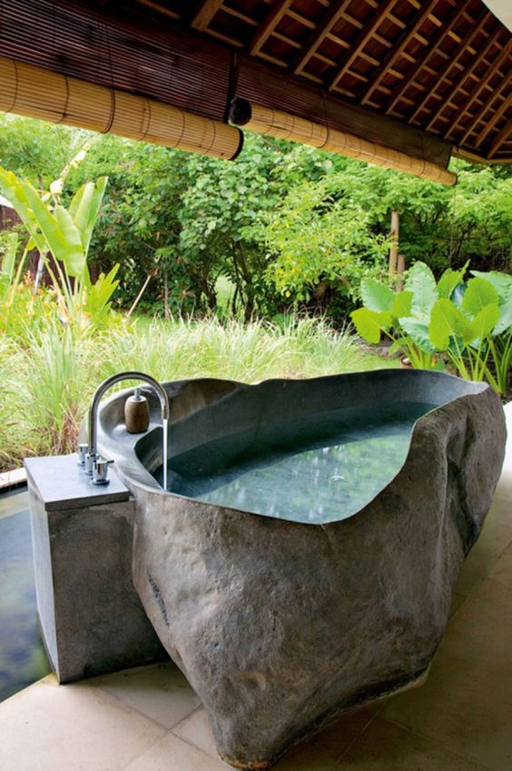 an outdoor stone bathtub with uneven edges will keep you cool outside durign hot days