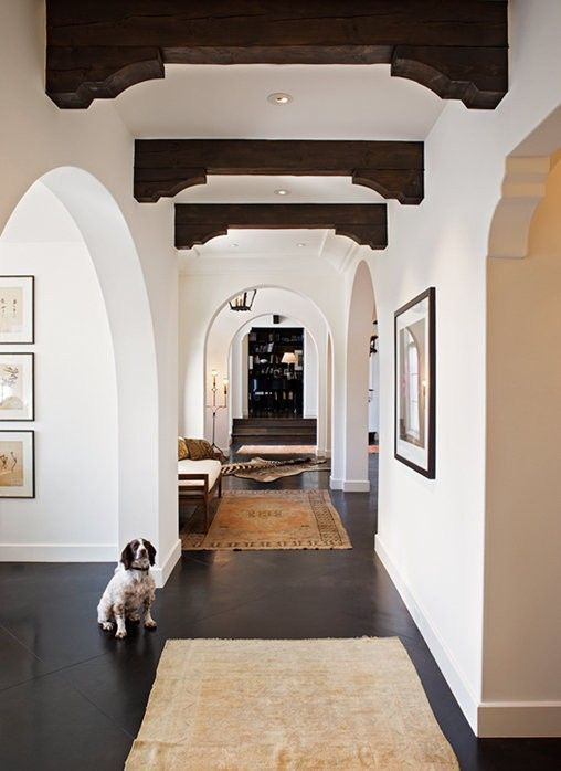 white plaster walls paired with dark floors and dark wooden beams plus arched doorways look very Spanish-like