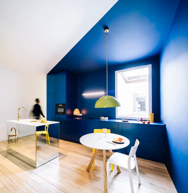 The kitchen features bold color blocking, bright blue and white walls, with a mirror kitchen island and a small breakfast space
