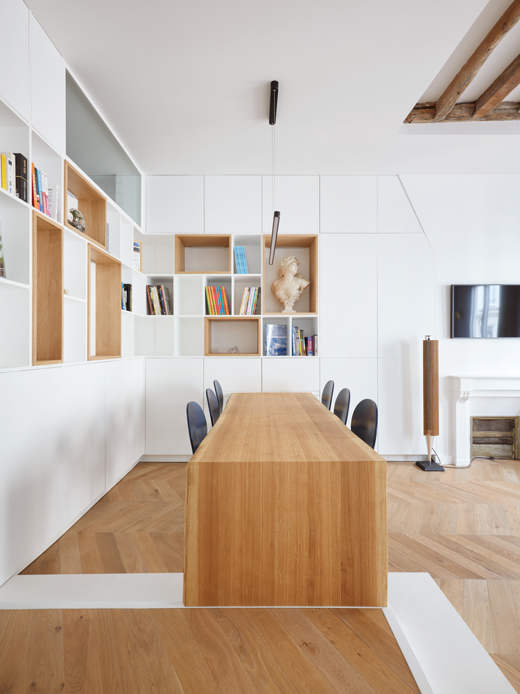 There are lots of storage units, open and closed sleek ones, and the dining table is a single and long slab of wood