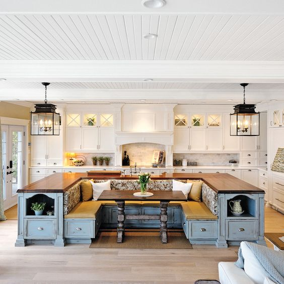 a farmhouse kitchen done in white with a blue kitchen island that includes storage and a seating area