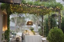 02 an outdoor dining room with a canopy of greenery and lights, candle lanterns, lots of potted greenery and wicker touches