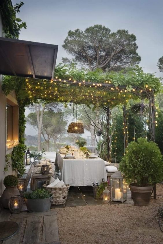 an outdoor dining room with a canopy of greenery and lights, candle lanterns, lots of potted greenery and wicker touches
