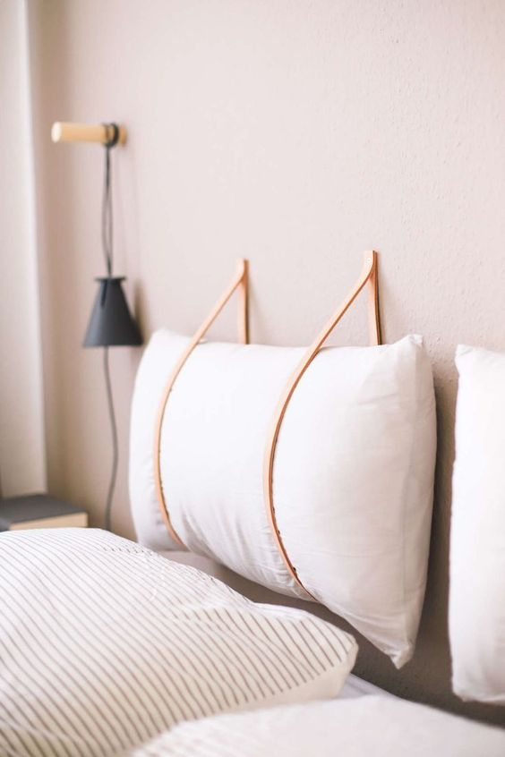 make a hanging headboard yourself hanging soem soft pillows on leather cords to secure them right