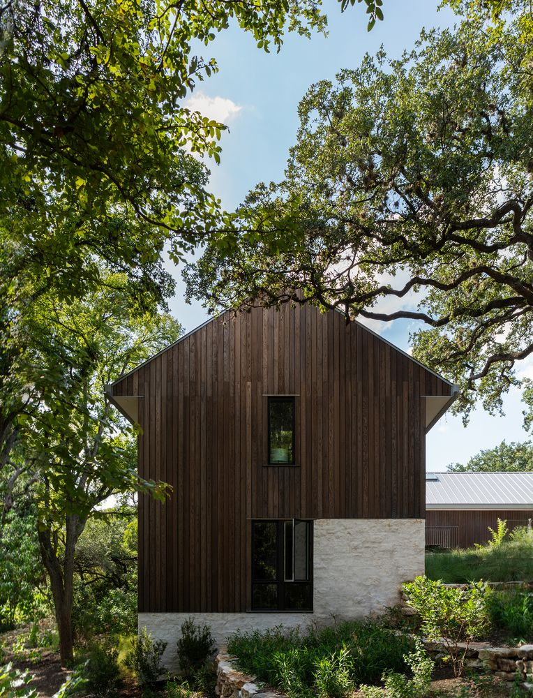The exterior of the house is clad with weathered wood and has a natural finish
