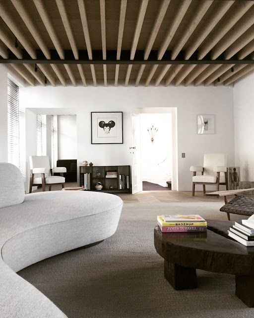 The living room features a curved sofa, a rough wooden table, a wooden plank ceiling, contemporary furniture and a neutral carpet