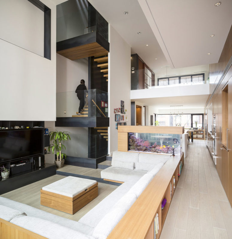 The living room is done with a sunken conversation space, with wooden furniture and a TV