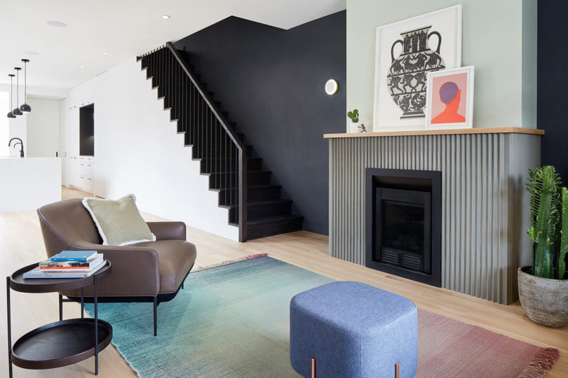 The living room is represented with a grene fireplace, comfy mid century modenr furniture and a gradient rug
