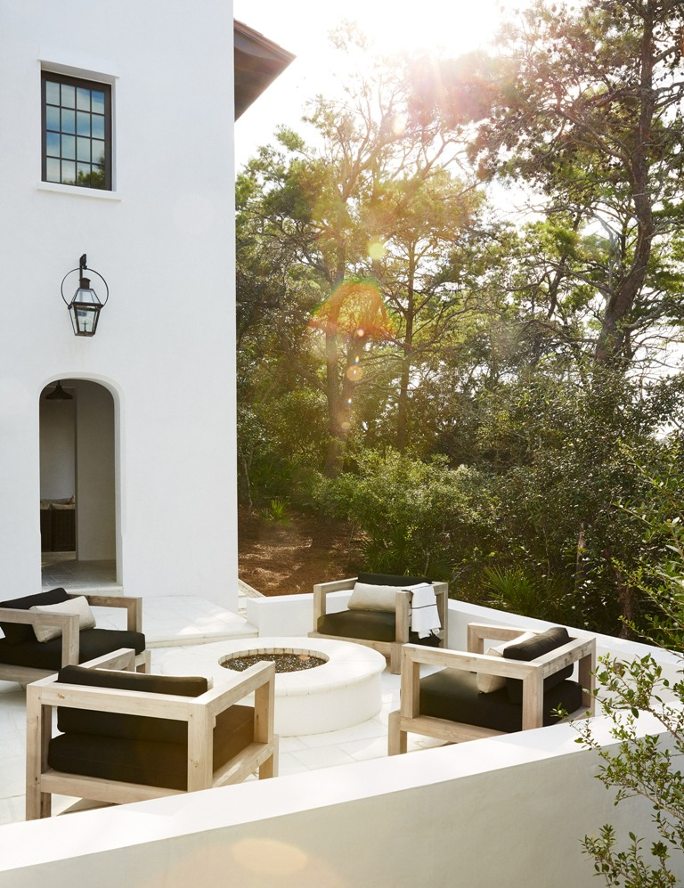 Thhe terrace is perfectly styled with black chairs and a fire pit in the center