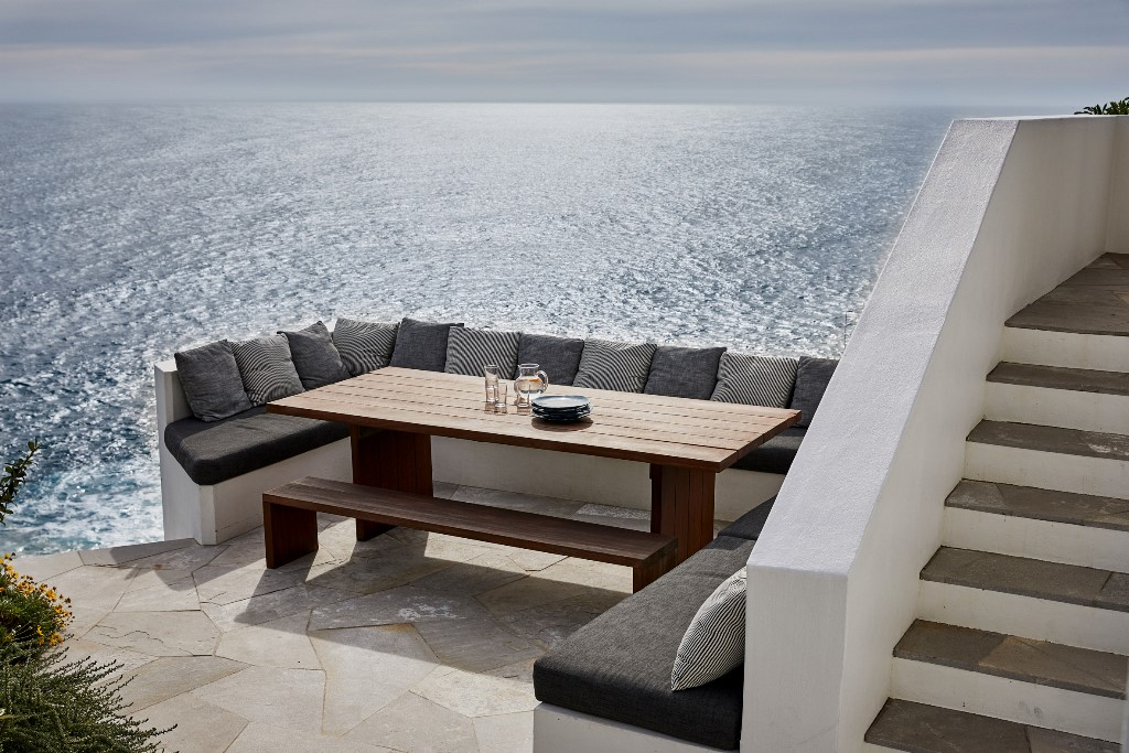 This is a cool outdoor dining space with a built in bench, a table and amazing views