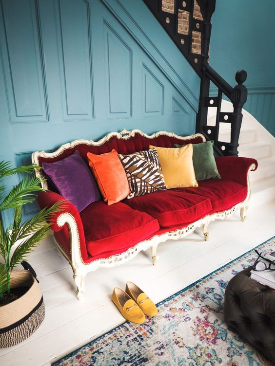 a bright eclectic entryway finished off with a bold vintage red sofa and colorful pillows