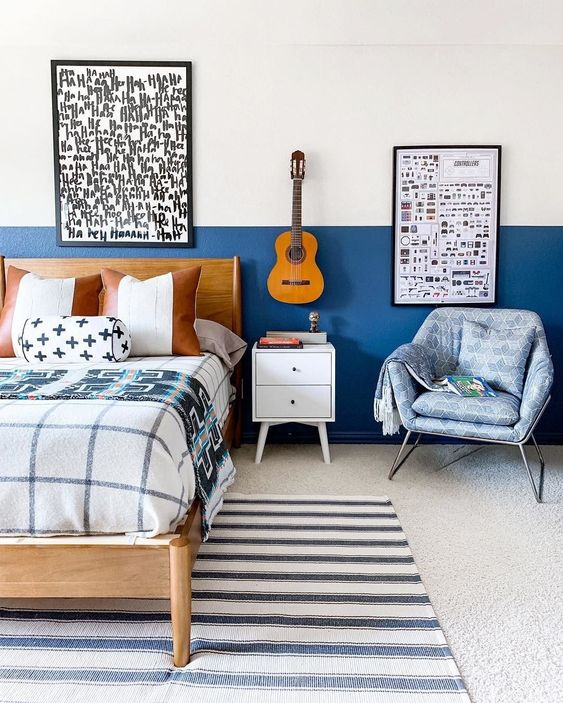 a small bedroom done with blueberry blue color blocking, graphic artworks and pritned textiles all over