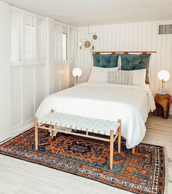 a white boho bedroom with a colorful rug and a blue pillow headboard on a copper holder for a touch of color