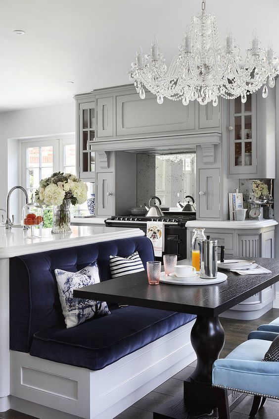 an eclectic kitchen with grey furniture, a white kitchen island with a navy seat built-in to compose a dining space