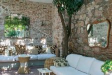 03 an outdoor living room with stone and brick walls, wicker and wooden furniture and greenery