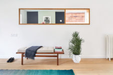 04 The entryway is clean and simple, with an upholstered bench and a potted plant in a geometric planter