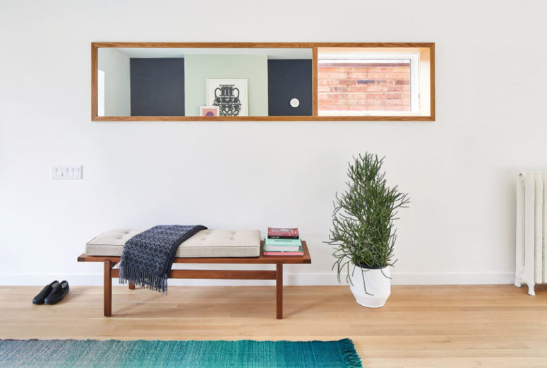 The entryway is clean and simple, with an upholstered bench and a potted plant in a geometric planter