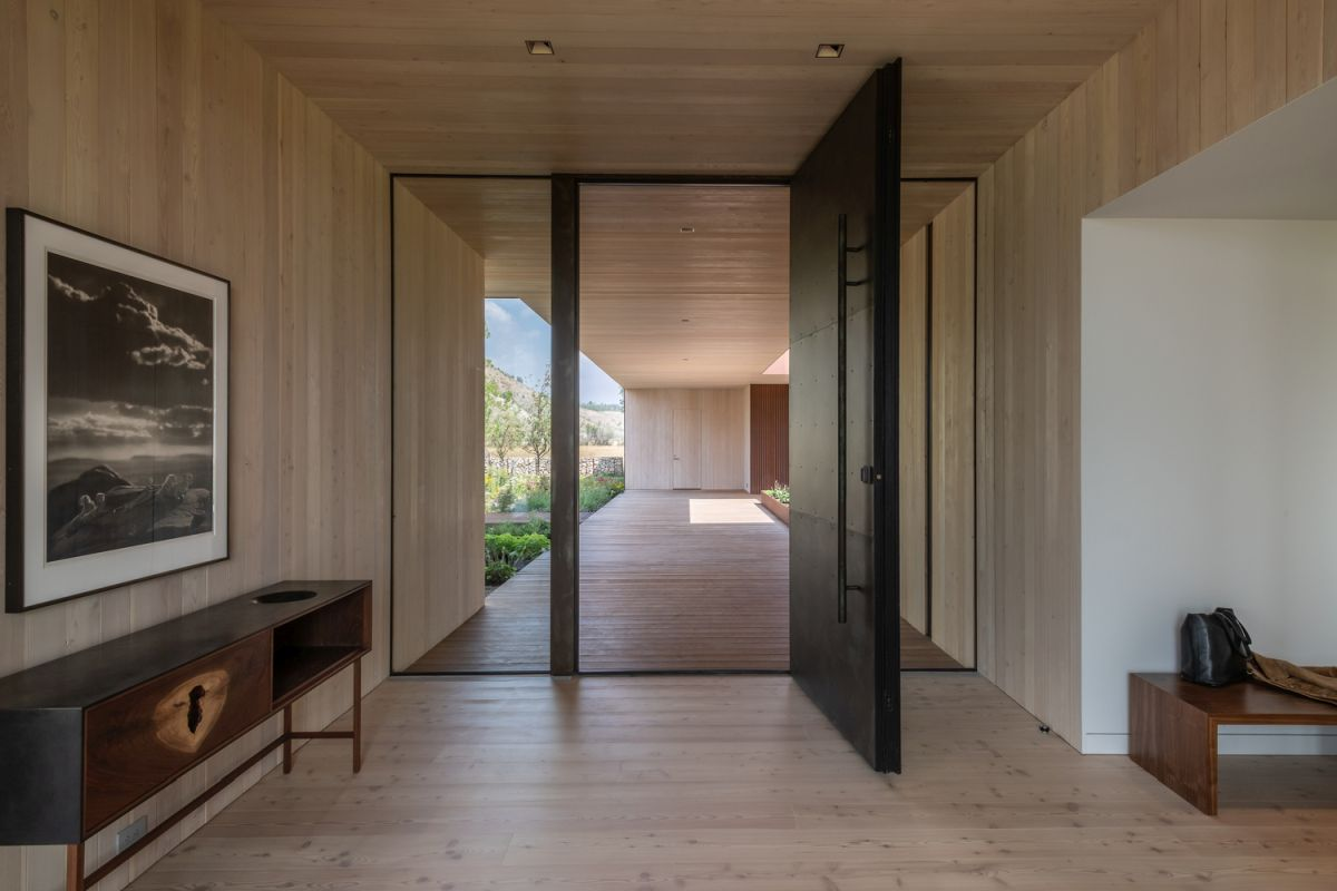 The entryway is minimalist, with a dark pivoting door and chic furniture, it's all done with light colored wood