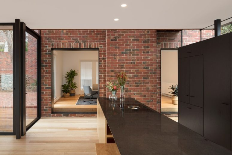 The kitchen is done dark, with chocolate brown cabinets and a kitchen island, a brick wall adds texture