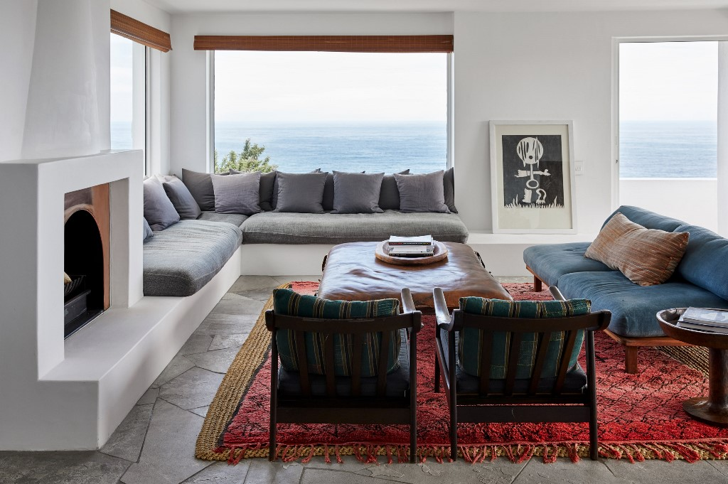 The living room decor continues the outdoor spaces with the same furniture, there's a fireplace and cool art