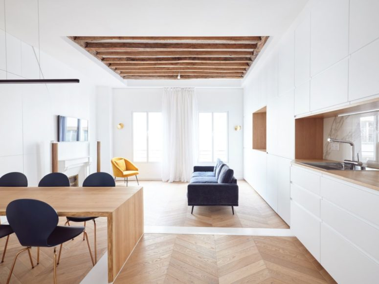 The living room is done with a faux fireplace, a blue sofa, a yellow chair and airy and light curtains, wooden beams on the ceiling add coziness