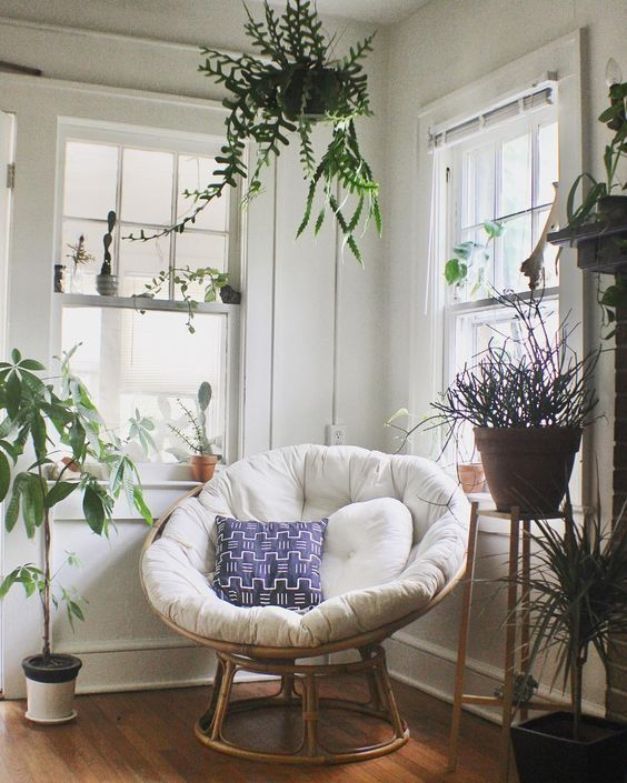 a chic nook with lots of potted plants and a papasan chair of rattan, with a neutral futon and bright pillows
