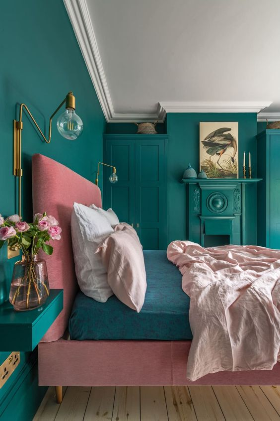 a colorful bedroom with brass wall sconces and some other brass touches that bring luxury and chic in