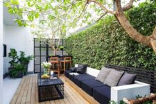 04 a contemporary outdoor living room with stylish furniture, a small bar and a living wall as a backdrop