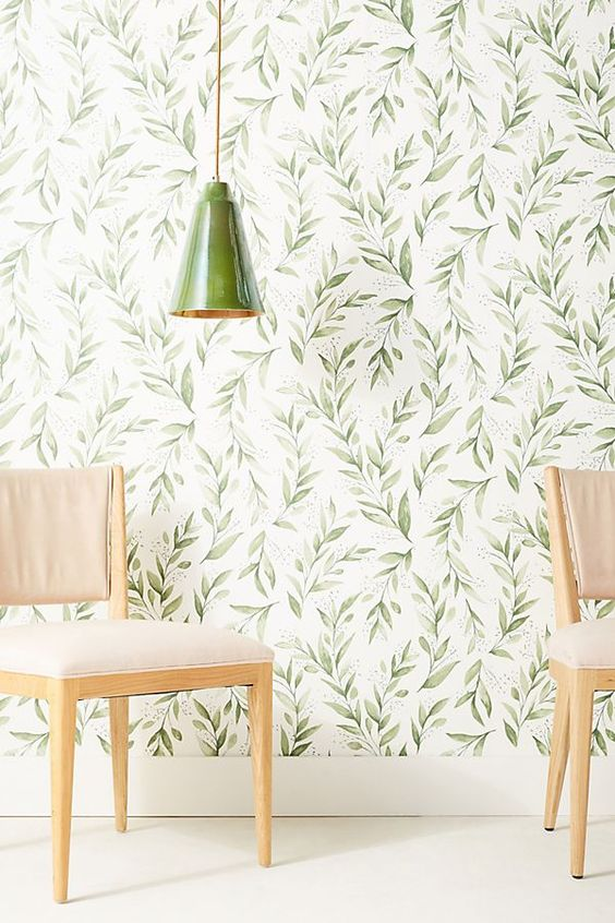 classic botanical wallpaper with a retro feel and a matching green porcelain lamp create a welcoming and cool space
