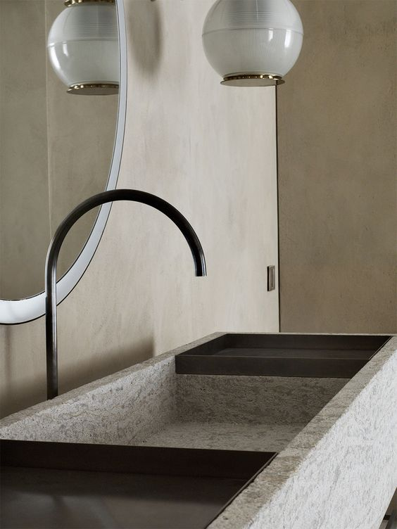 The bathroom is done with neutral plywood panels, with a textural stone sink and an elegant pendant lamp