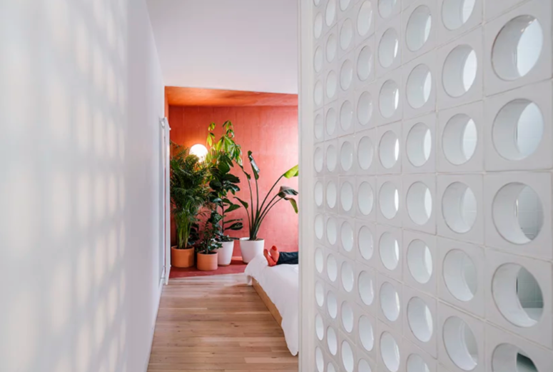 The bedroom is separated with a perforated wall and features a red color blocked zone