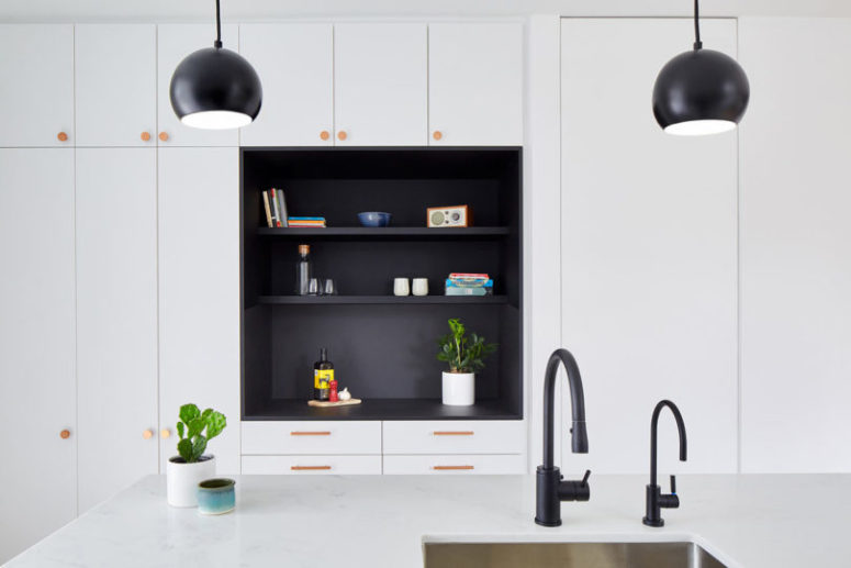 The kitchen is done in white, with wooden knobs and a black niche in the center to make a statement