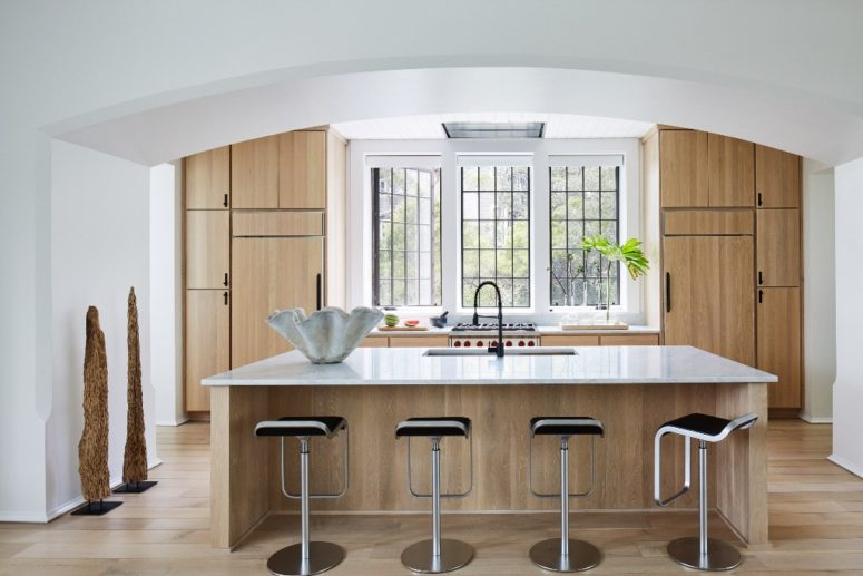 The kitchen is done with light-colored wooden cabinets and a kitchen island plus a large window instead of a backsplash
