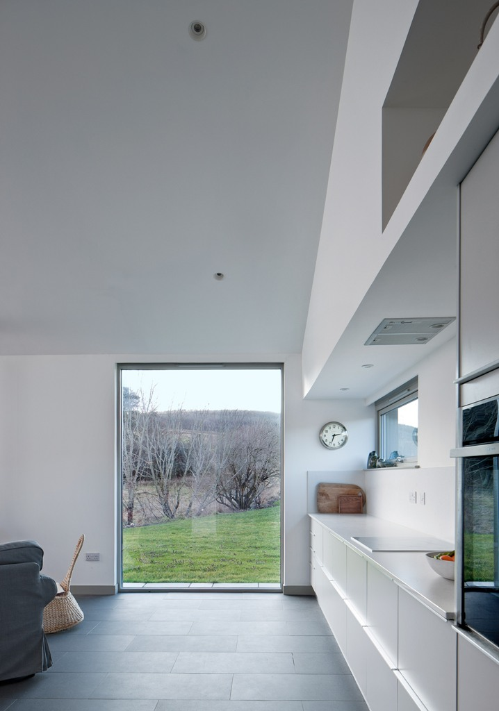 The kitchen is done with sleek white cabinets, there's a large window and a window backsplash